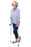 Bebrillte alte Frau, die mit Krücken geht lizenzfreie stockfotos