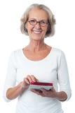 Bebrillte Dame, die mit Tabletten-PC aufwirft Stockbild