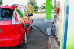 Bec de pompe à gaz dans le réservoir de carburant d'une voiture Image stock