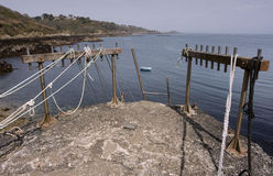 bec du Nez,与停泊绳索和梯子的跳船海岸边缘,看法, Fermaine海湾和圣伯多禄口岸堡垒,根西岛。 库存图片