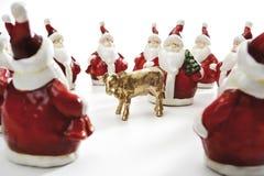 Becerro de oro, rodeado por Santa Clauses Foto de archivo