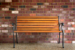 Bech against a brick wall. Serene image of a park bench against a brick wall with ample copy space Stock Image