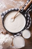 Bechamel sauce in a pan and flour, milk on the table top view. Bechamel sauce in a pan and flour, milk on the table. vertical top view close-up royalty free stock photography