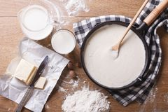 Bechamel sauce in a pan and ingredients horizontal top view. Preparation of bechamel sauce in a pan and ingredients on the table. horizontal view from above royalty free stock photos