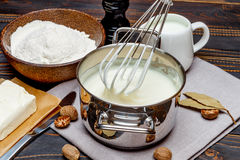 Bechamel sauce in a pan and ingredients Stock Images