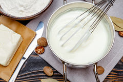 Bechamel sauce in a pan and ingredients. Preparation of bechamel sauce in a pan and ingredients on the wooden table royalty free stock image