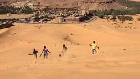 BECHAR, ARGÉLIA - 29 DE OUTUBRO DE 2016: os meninos estão correndo o vídeo de movimento lento em declive no deserto de Taghit, No video estoque