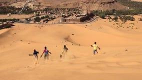 BECHAR, ARGELIA - 29 DE OCTUBRE DE 2016: los muchachos están funcionando con el vídeo en declive en el desierto de Taghit, África almacen de video