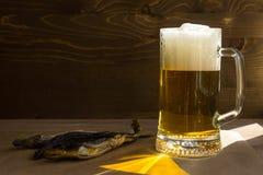 Becher Bier auf einem Holztisch und einem Trockenfisch Stockfotografie