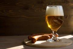 Becher-Bier auf einem Holztisch und einer Wurst Stockfotos