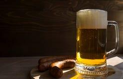Becher-Bier auf einem Holztisch und einer Wurst Lizenzfreie Stockfotografie