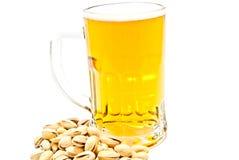 Becher Bier und geschmackvolle Pistazien lizenzfreie stockbilder