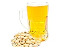Becher Bier und Pistazien auf Weiß stockfotografie
