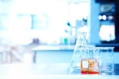 Becher de flacon avec la solution orange dans l'éducation de recherches de la science photo stock