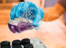Becher in der Wissenschaftlerhand mit Ausrüstung und Wissenschaft experimentiert Lizenzfreies Stockbild