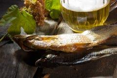 Becher des Bieres und des Trockenfisches Stockbild
