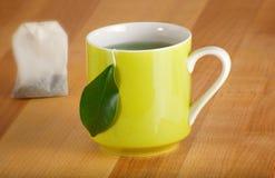 Becher des organischen grünen Tees und des Teebeutels Stockfotos