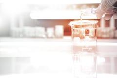 Becher en verre avec l'eau et la main étudiante à fond du scientifique du cylind photo stock