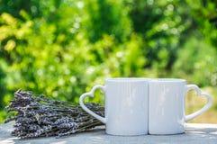 Becher für Liebhaber Zwei romantische Schalen Zwei weiße Schalen mit Herzen Lizenzfreies Stockfoto