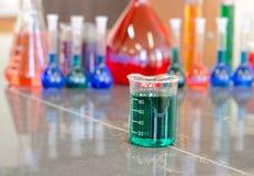 Becher gefüllt mit grüner Chemikalie stockbilder