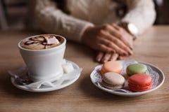 Becher heißer Cappuccino wird schön, die Kunst des Kaffees, Makrone verziert Lattekaffee mit macarons Lizenzfreie Stockfotografie