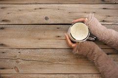 Becher heißer Kaffee in den Frauenhänden stockfotografie