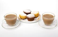 Becher Kaffee und kleine Kuchen Stockbilder