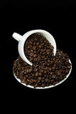 Becher Kaffeebohnen mit Untertasse auf schwarzem Hintergrund Stockbild