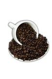 Becher Kaffeebohnen mit Untertasse auf weißem Hintergrund Lizenzfreies Stockfoto