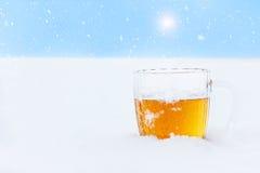 Becher kaltes Bier auf dem Schnee Stockfotos