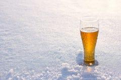 Becher kaltes Bier im Schnee bei Sonnenuntergang Schöner Winterhintergrund Im Freienerholung Lizenzfreies Stockbild
