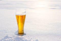 Becher kaltes Bier im Schnee bei Sonnenuntergang Schöner Winterhintergrund Im Freienerholung Lizenzfreies Stockfoto