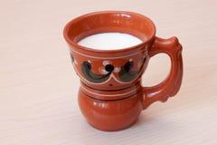 Becher mit Milch auf dem Tisch Stockbild