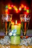 Becher mit Sekt und einer brennenden Kerze Stockbilder