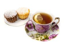 Becher Tee mit Zitrone und und zwei kleinen Kuchen Stockbilder