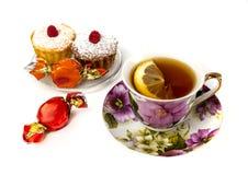 Becher Tee mit Zitrone und und zwei kleinen Kuchen Lizenzfreie Stockbilder