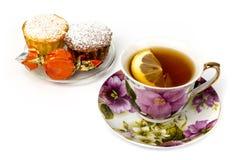 Becher Tee mit Zitrone und und zwei kleinen Kuchen Lizenzfreies Stockbild