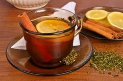 Becher Tee mit Zitrone und Zimtstange Stockfotografie