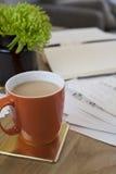 Becher Tee oder Kaffee auf Arbeitsfläche mit Notizbüchern und Papiere und eine Anlage Lizenzfreie Stockfotografie