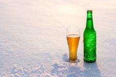Becher und Flasche kaltes Bier im Schnee bei Sonnenuntergang Schöner Winterhintergrund Im Freienerholung Lizenzfreie Stockbilder