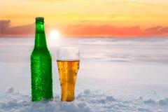 Becher und Flasche kaltes Bier im Schnee bei Sonnenuntergang Schöner Winterhintergrund Im Freienerholung Stockfoto