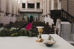 Becher Wein auf Tabelle während einer Heiratszeremoniebrautmesse Buch und Kreuz Katholische Verzierungen des heiligen Abendmahl f stockfoto