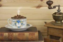 BecherKaffeebohnen und alte Bücher sind im Regal Stillstehender Komfort über Kaffee und dem Ablesen Stockfotos