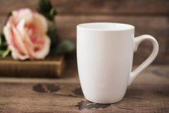 Bechermodell Kaffeetasseschablone Kaffeetasse-Druckdesign-Schablone Weißes Becher-Modell, altes Buch und Blume Stockfoto