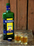 Becherovka bottle and two glasses of an alcoholic beverage on a wooden background Stock Images