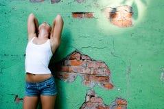 Becide da menina a parede Fotografia de Stock