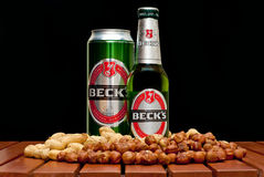 Beck's beer. ZAGREB , CROATIA - JANUARY 24 ,2014 :  Beer bottle and can on black background, Beck's with peanuts and huzelnuts on the table, product shot Stock Photo