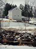 Beckman Mill. Framed between  trees in the winter forest with snow on the ground with rocks and an icy lake in the foreground Royalty Free Stock Images