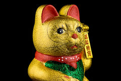 Beckoning Cat With Black Background. Beckoning Cat, studio shot of golden asian figurine with black background royalty free stock photography