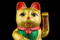 Beckoning Cat With Black Background. Beckoning Cat, studio shot of golden asian figurine with black background stock photo